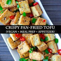 Close-up top view of a plate with fried tofu cubes garnished with chopped spring onion, red chili, and toasted white sesame seeds.
