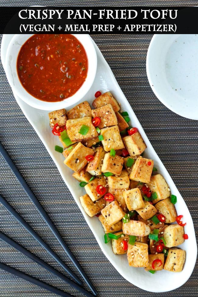 A long white plate with a bowl of spicy dipping sauce and pan-fried tofu cubes sprinkled with chopped spring onion, chopped red chili, and toasted white sesame seeds. Black chopsticks and small plates on either side of the plate.