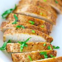 Close up of a sliced seasoned and baked chicken breast fanned out in a white round plate and garnished with fresh chopped parsley.