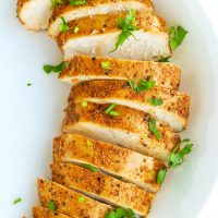 A sliced seasoned and baked chicken breast fanned out in a white round plate and garnished with fresh chopped parsley.