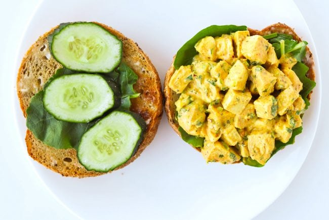 10 cereal bagel halves on a plate with salad greens, cucumber slices, and mango chicken salad.