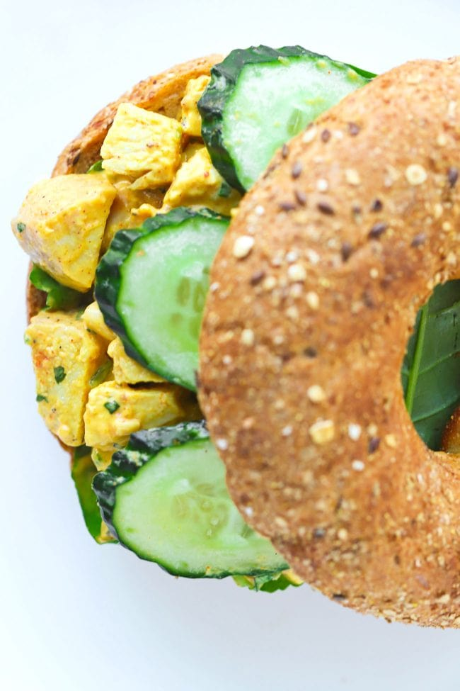 Top view of a mango chicken salad bagel sandwich with spinach leaves and cucumber slices on a white plate.