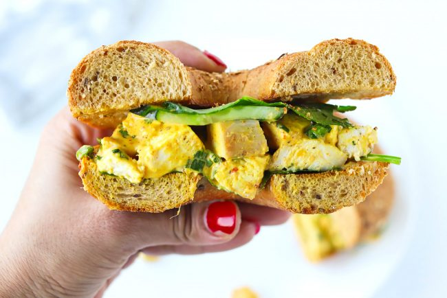 Hand holding up half of a bagel sandwich with mixed greens, cucumber slices, and mango chicken salad.