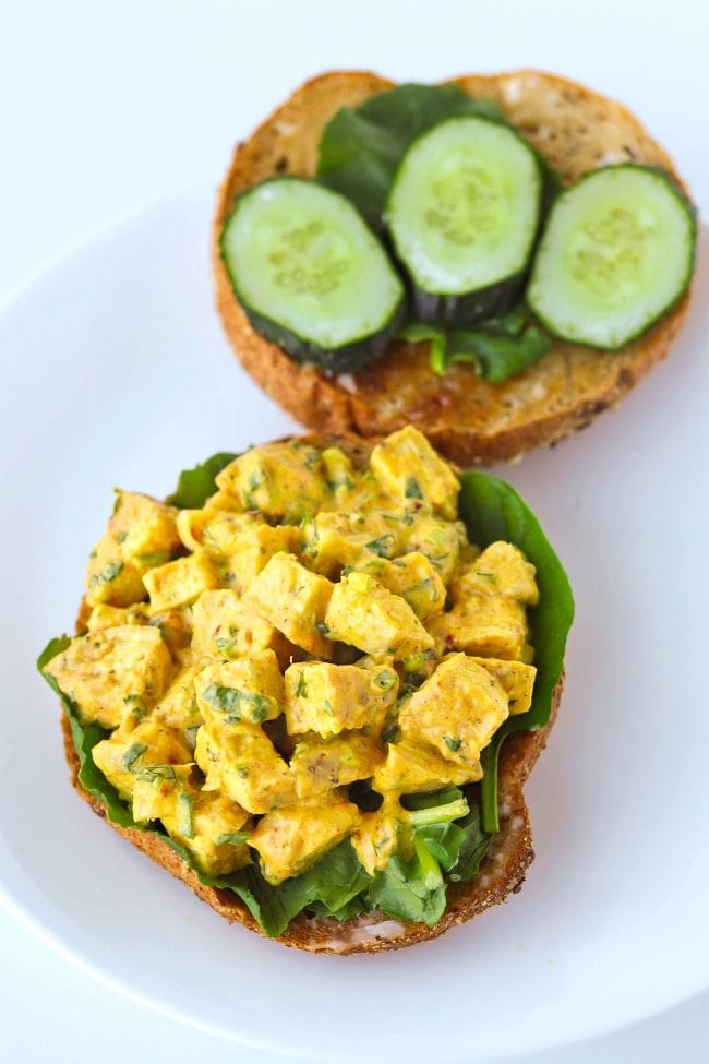 10 cereal bagel halves on a plate with spinach leaves, cucumber slices, and mango chicken salad.
