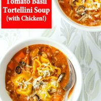 Two diagonally placed bowls of creamy tomato basil soup with tortellini, ground chicken, pinto beans, diced carrot, and sliced black olives topped with grated cheese. Bowl in front has a silver spoon.