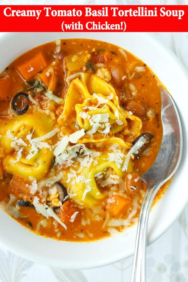 Close up of tomato basil tortellini soup with pinto beans, ground chicken, and sliced black olives topped with grated cheese in a white round bowl with a silver spoon.