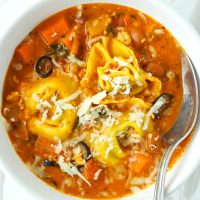Tomato basil tortellini soup with chicken, pinto beans, diced carrot, and sliced black olives topped with grated cheese in a white round bowl with a silver spoon.