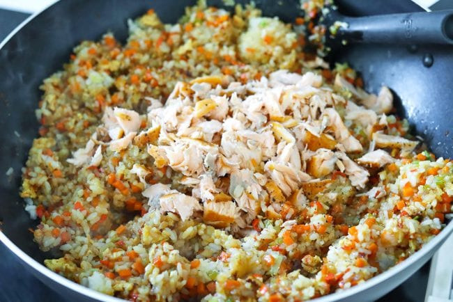 Flaked pan-fried salmon on top of fried rice with chopped carrots, celery, ginger, garlic, red chilies, spring onion whites, and scrambled eggs.