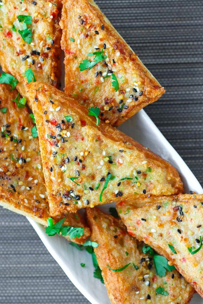 Close up of Spicy Prawn Toast triangles with Everything Bagel Seasoning on a long plate garnished with chopped coriander.