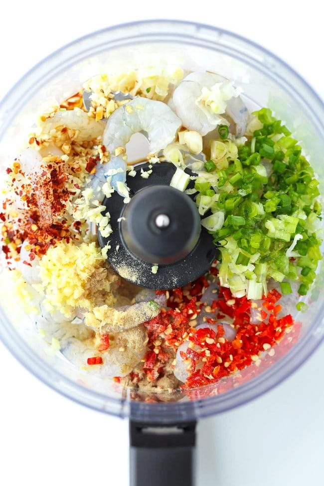 Prawns, chopped spring onion, red chilies, garlic, ginger, white pepper, salt, crushed red pepper flakes, sesame oil, soy, sauce, and shao xing rice wine in a food processor bowl