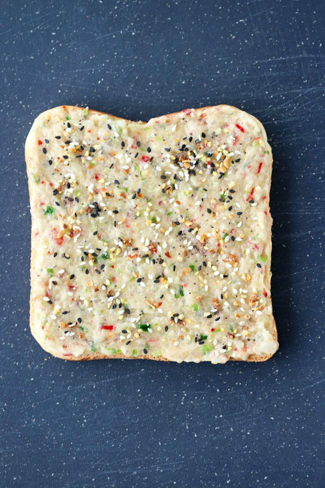 A slice of sandwich bread with spicy prawn paste and sprinkled with Everything Bagel Seasoning on top of a cutting board.