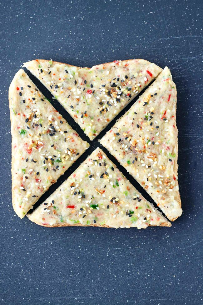 A slice of sandwich bread with spicy prawn paste and sprinkled with Everything Bagel Seasoning sliced into four triangles on top of a cutting board.