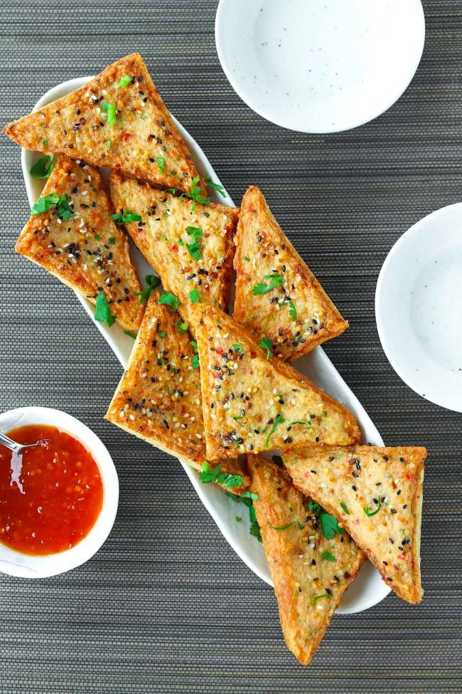 Spicy Prawn Toast triangles with Everything Bagel Seasoning on a long plate garnished with chopped coriander. Small bowl with Thai Sweet Chili Sauce and small plates on the side.