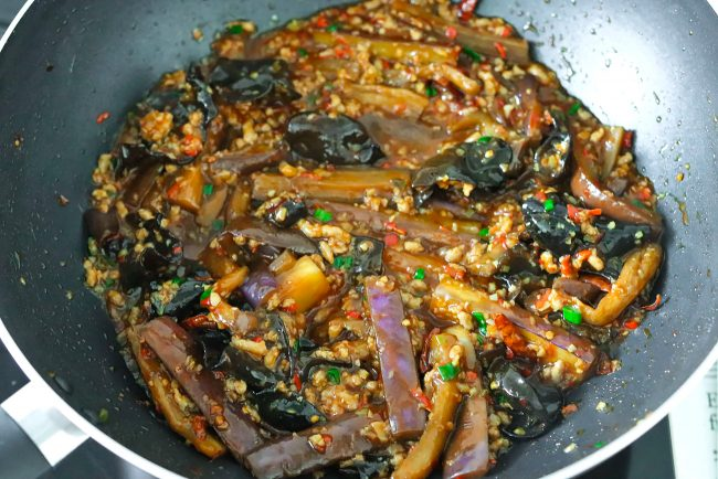 Yu Xiang Eggplant, ground pork, cloud ear mushrooms, and aromatics being stir-fried in a wok on the stovetop.