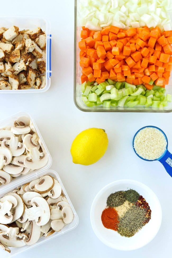 Containers with cooked seasoned chicken pieces, mushrooms. Diced onion, carrots, and celery in a glass dish. Seasonings and spices in a bowl, measuring cup with rice, and a lemon.