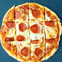 A pepperoni pizza with red onion slices cut into squares on top of a blackish-blue cutting board.