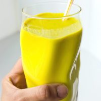 Hand holding up a glass with yellow turmeric milk with spices and a straw.