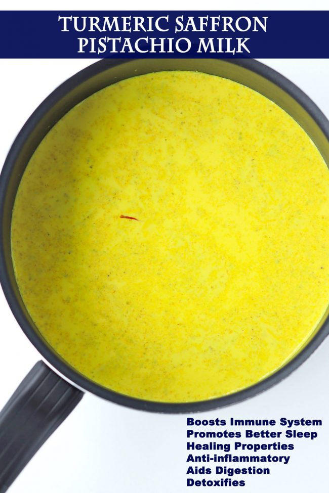 Yellow turmeric milk with spices in a black saucepan.