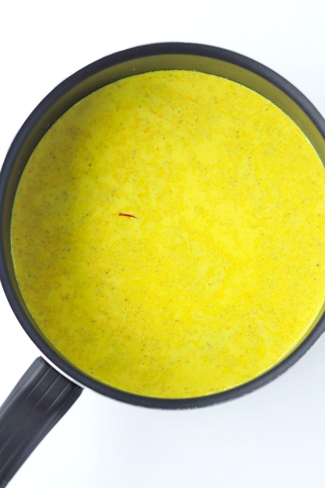 Yellow turmeric milk with spices in black saucepan.