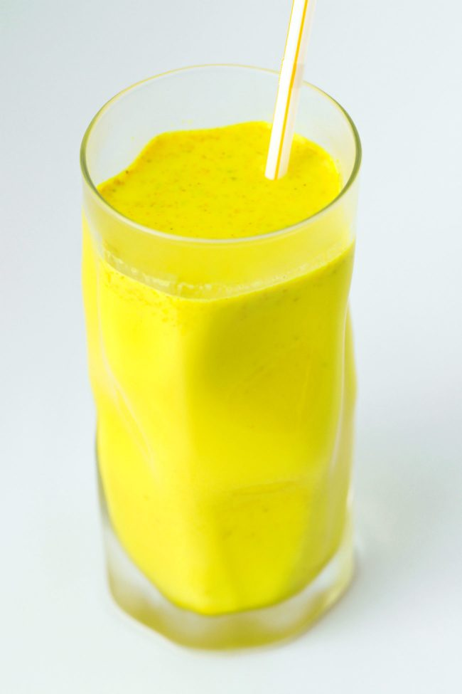 Yellow turmeric milk with spices in a tall fancy glass with a straw.