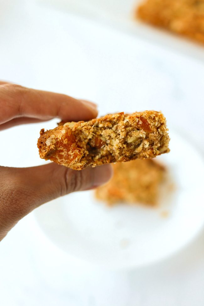 Hand holding up an apricot and almond oat slice with a bite taken out of it.