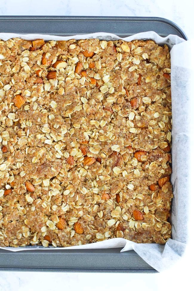 Apricot almond oat mixture flattened down in a parchment paper lined baking pan.