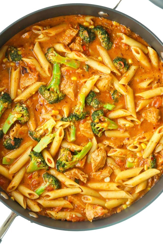 Deep large sauté pan with penne pasta, spicy tomato BBQ sauce, broccoli florets, corn, and chicken pieces.