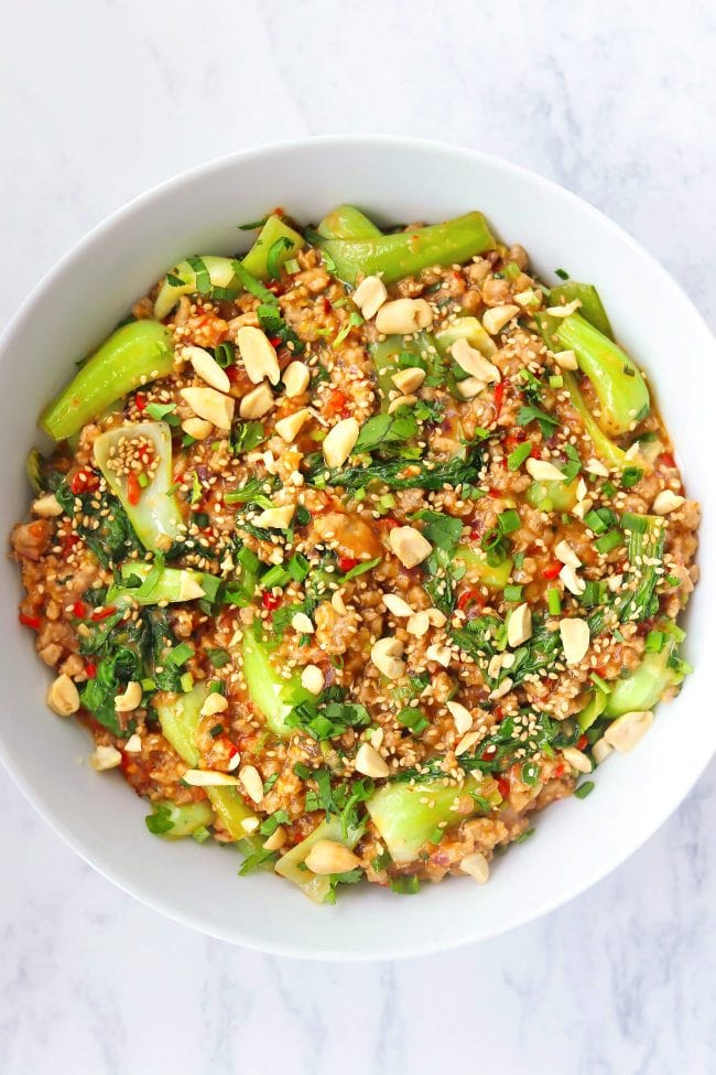 Ground pork and bok choy in peanut sauce in a white round serving bowl topped with sesame seeds, chopped peanuts, coriander, and spring onion.