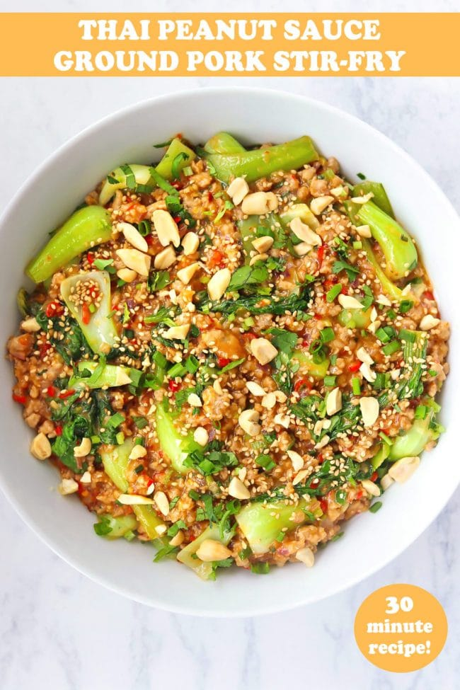 Minced meat and bok choy peanut sauce stir-fry in round white serving bowl topped with sesame seeds, chopped peanuts, coriander, and spring onion. Serving bowl with the stir-fry and bowl with peanuts in the back.