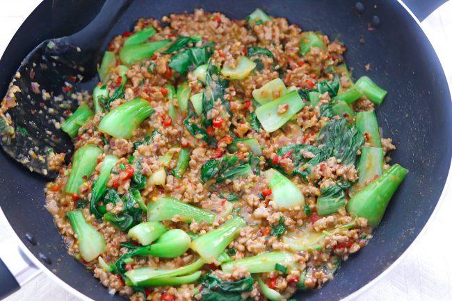 Ground pork and bok choy peanut sauce stir-fry in wok with spatula.