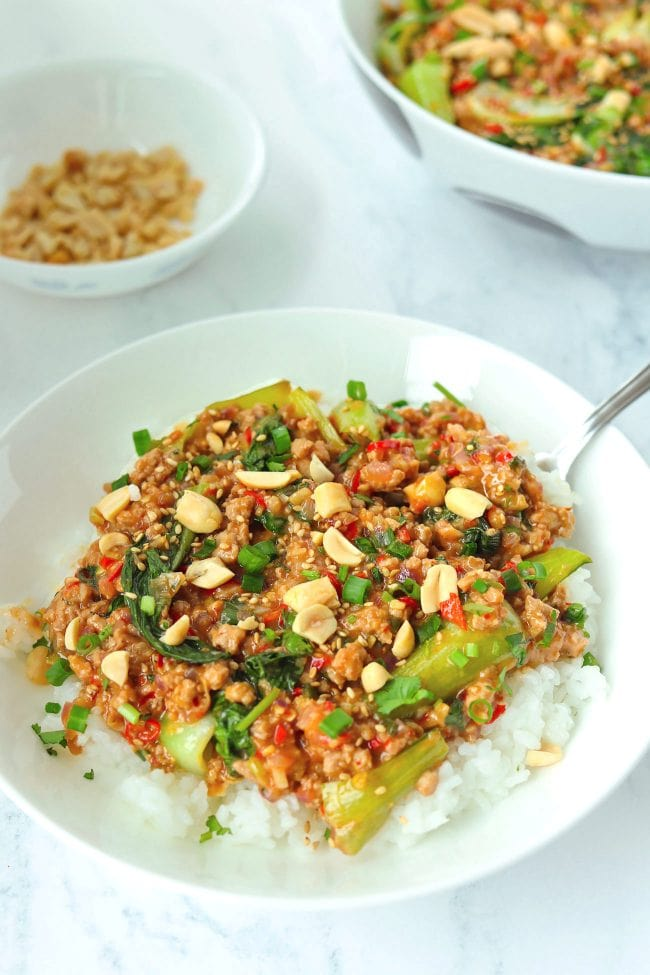 Minced pork and bok choy peanut sauce stir-fry on plate with rice and spoon, topped with sesame seeds, chopped peanuts, coriander, and spring onion. Serving bowl with the stir-fry and bowl with peanuts in the back.