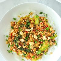 Ground pork and bok choy peanut sauce stir-fry on rice in plate and topped with sesame seeds, chopped peanuts, coriander, and spring onion. Serving bowl with the stir-fry and bowl with peanuts in the back.