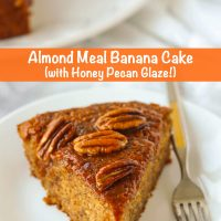 Slice of almond banana cake topped with honey pecan glaze and a fork on a small white plate. Whole cake on a large plate in the back.