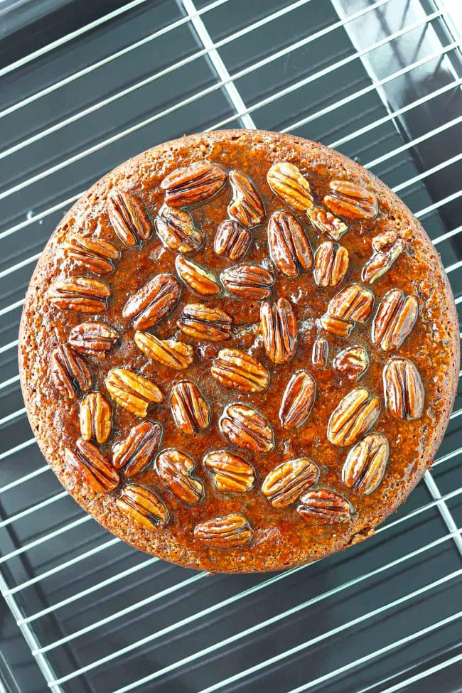 Whole Almond Banana Cake topped with honey pecan glaze on a cooling rack on top of baking tray.