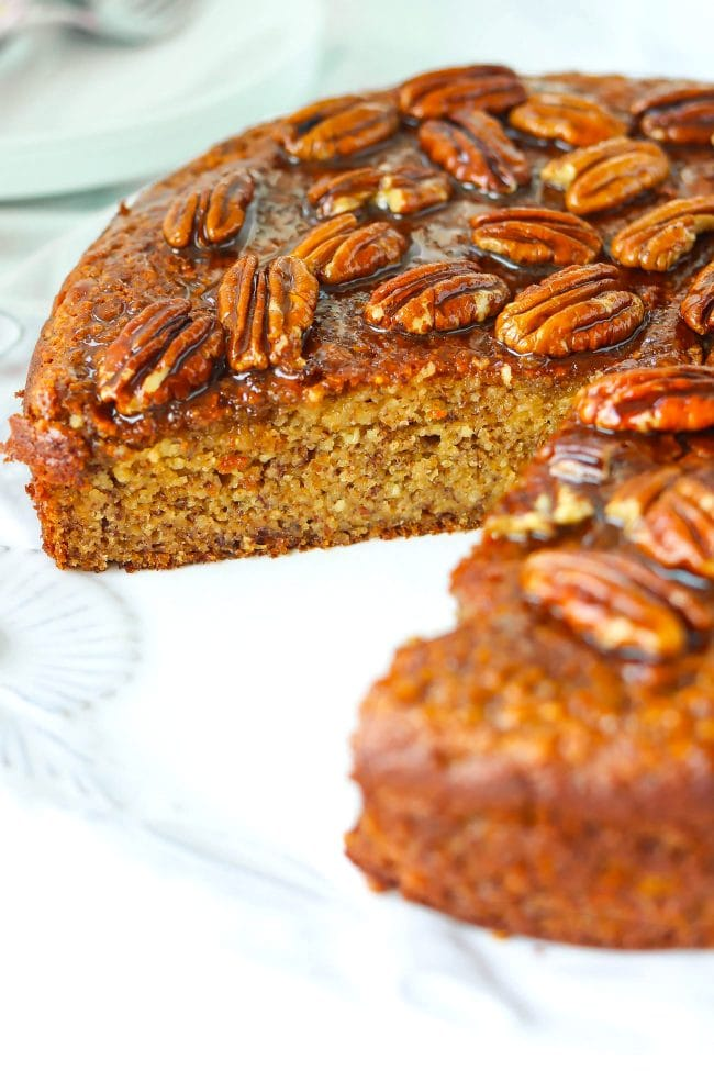 Almond cake with honey pecan glaze on a large round plate with a slice cut out to show the  texture inside.