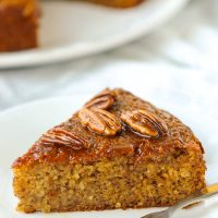 Side view of a slice of almond banana cake topped with honey pecan glaze and a fork on a small white plate. Rest of the cake on a large plate in the back.