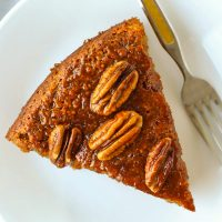 Top view of a slice of almond banana cake topped with honey pecan glaze and a fork on a small white plate.