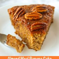 Front view of almond meal banana cake with honey pecan glaze on a small white plate with a fork with a bite on it.