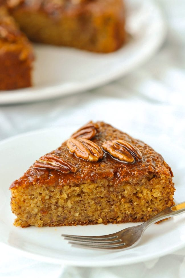 Side view of a slice of moist cake topped with honey pecan glaze and a fork on a small white plate. Rest of the cake on a large plate in the back.
