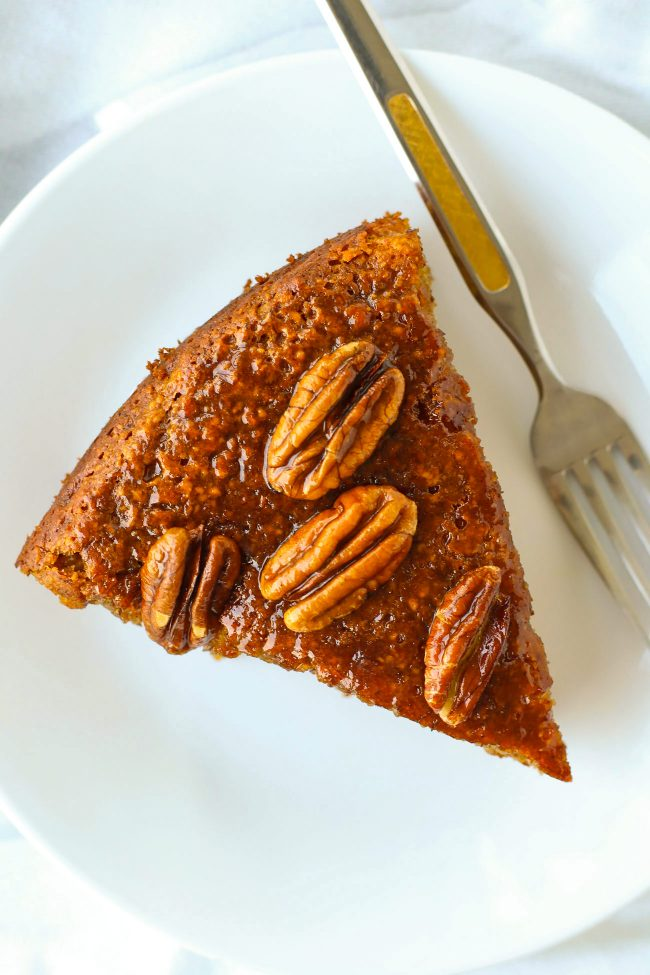 Top view of slice of almond banana cake topped with honey pecan glaze and a fork on a small white plate.
