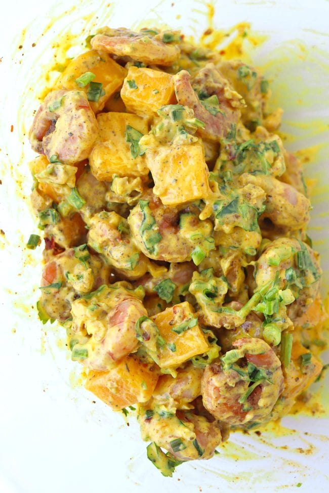 Cajun shrimp, cubed mango, creamy spicy mango mayonnaise, chopped coriander, spring onion, and walnuts tossed together in a large mixing bowl.