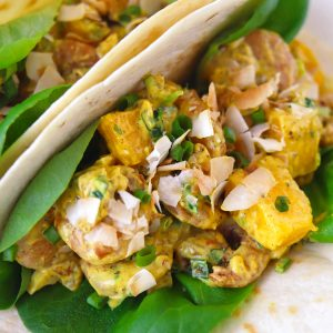 Two Cajun Shrimp Mango Tacos with butter lettuce and sprinkled with toasted coconut flakes folded on a white round plate.