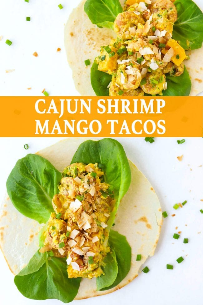 Two open-faced Cajun Shrimp Mango Tacos with butter lettuce and topped with toasted coconut flakes on a white background. Spring onion and coconut flakes scattered around the tacos.