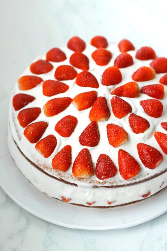 Whole strawberry cream cake on a platter.