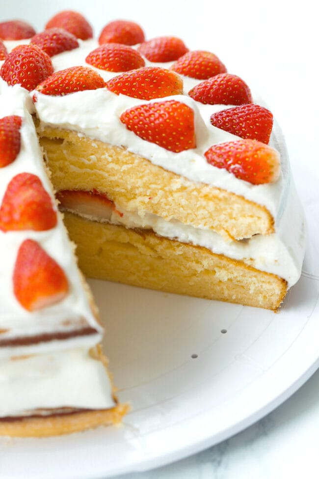 Strawberry cream cake on a platter with a slice cut out to show inside of cake.