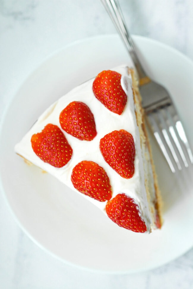 Top view of a slice of strawberry cream cake and a fork on a white round plate.