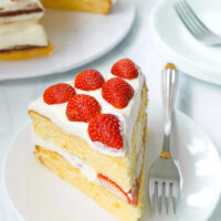 """Front view of a slice of cake on a plate with a fork. Text overlay """"Strawberry Lemon Cream Cake""""."""