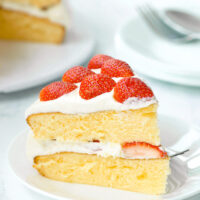 """Left side view of slice of two layer cake on a plate with a fork. Text overlay """"Strawberry Lemon Cream Cake""""."""