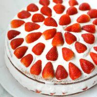 "Whole strawberry lemon cream two layer cake on a platter. Text overlay ""Strawberry Lemon Cream Cake""."
