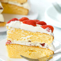 """Side view of slice of strawberry lemon cream layer cake on a plate with a fork. Text overlay """"Strawberry Lemon Cream Cake""""."""